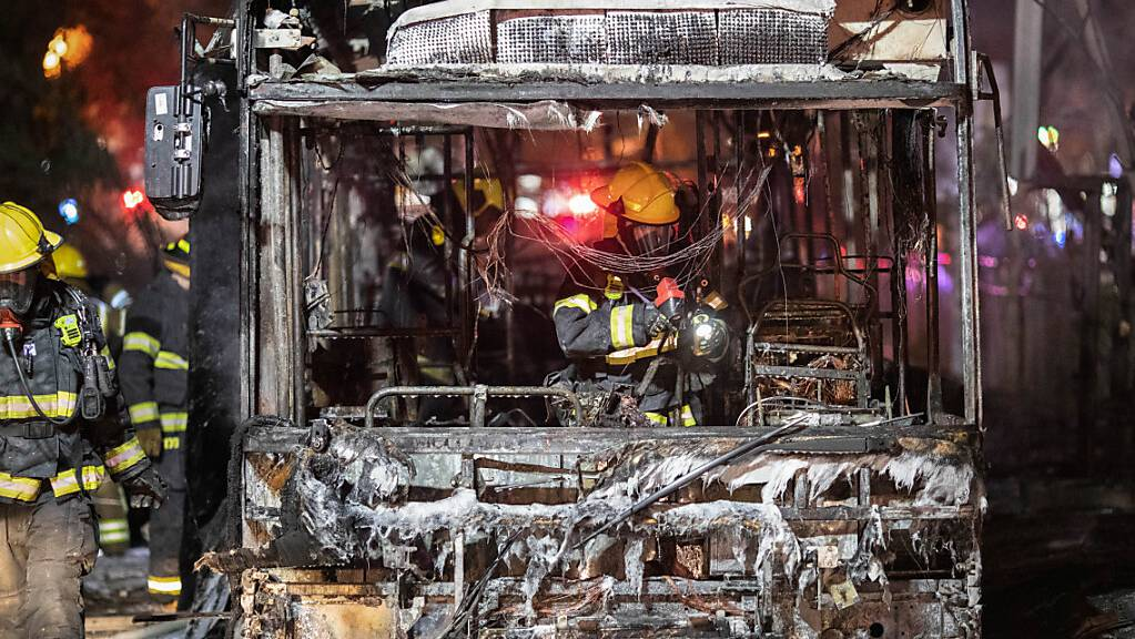 Israelische Feuerwehrleute inspizieren in Holon südlich von Tel Aviv einen verbrannten Bus, der von einer Rakete getroffen wurde. Foto: Oren Ziv/dpa