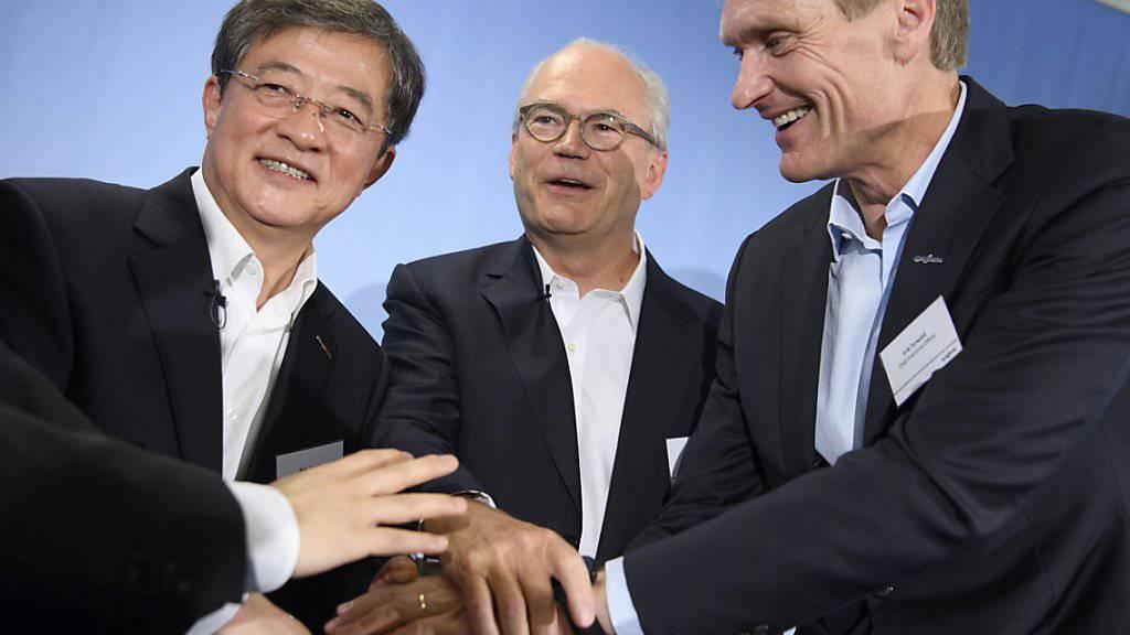 Bisher kauften chinesische Investoren vor allem Grosskonzerne wie Syngenta, nun nehmen sie laut UBS-Experten auch kleinere Übernahmeziele ins Visier. Im Bild: Das damalige Syngenta-Management besiegeln mit ChemChina den Deal per Handschlag. (Archivbild)