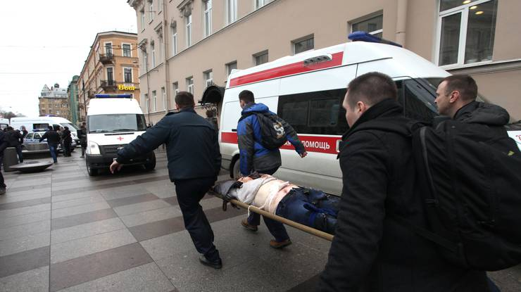 Menschen tragen eine verletzte Person weg.
