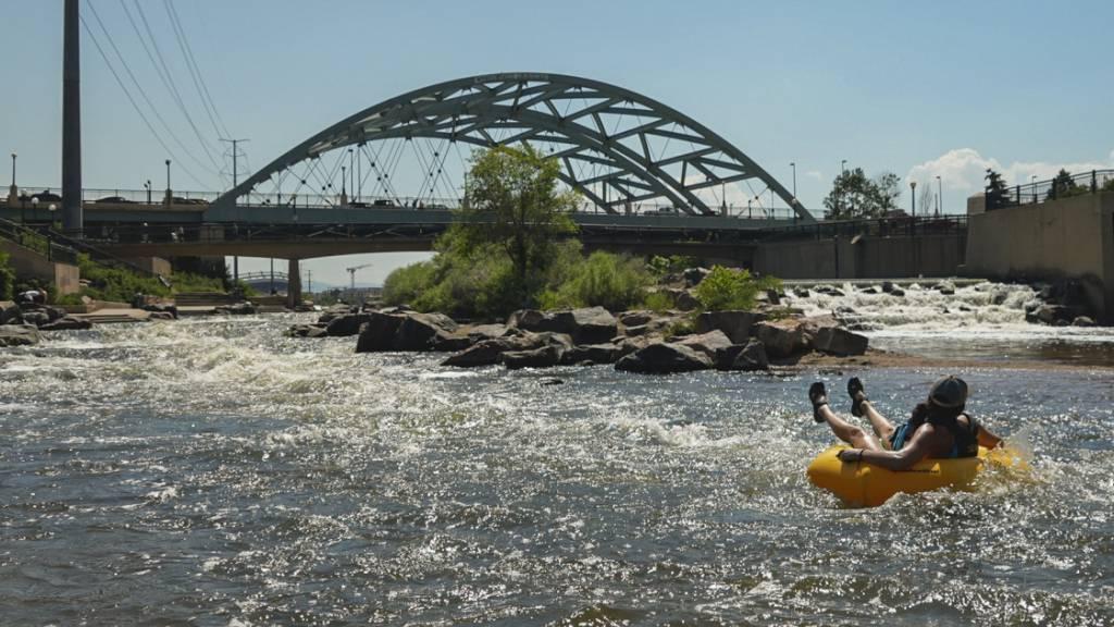 Menschen kühlen sich im Wasser ab, am Zusammenfluss von South Platte River und Cherry Creek. Am Nachmittag erreichte die Temperatur 35 Grad Celsius als Teil der Hitzewelle, die über den Westen der USA hinwegfegt. Foto: Brittany Peterson/AP/dpa