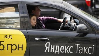 Eine Frau fährt in einem Yandex-Taxi mit. In Russland spannt Konkurrent Uber nun mit dem russischen Internetkonzern zusammen, um den Markt zu erschliessen. (Archiv)