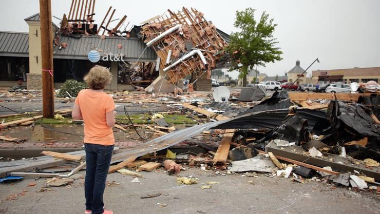 Eine Frau steht vor den Trümmern ihres Hauses.