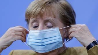 Bundeskanzlerin Angela Merkel (CDU) setzt ihre Gesichtsmaske nach ihrer Pressekonferenz auf. Foto: Odd Andersen/AFP/POOL/dpa