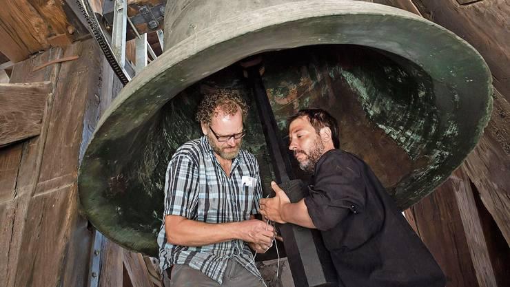Techniker Gabriel Schneider (links) und Schlagzeuger Peter Conradin Zumthor bringen einen Dämpfer an einer Glocke der Hofkirche an.