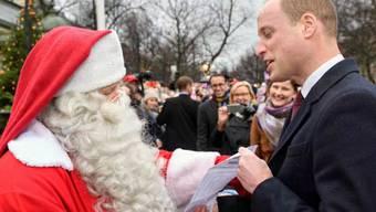Prinz William übergibt dem Weihnachtsmann in Finnland die Wunschliste seines Sohnes.