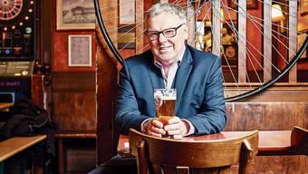 Ian Nicol in seinem Pub. Hinter ihm ein Hochrad, auf Englisch: Penny Farthing. Bil