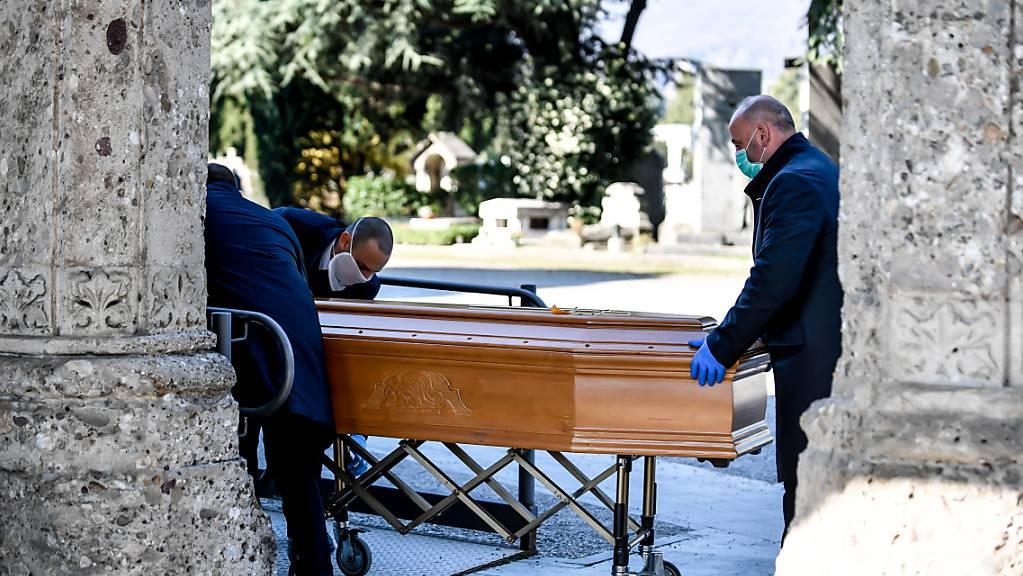ARCHIV - Mitarbeiter eines Bestattungsunternehmens schieben einen Sarg. Foto: Claudio Furlan/LaPresse via ZUMA Press/dpa