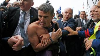 Ohne Hemd: Bodyguards lotsen Air-France-Personalchef Xavier Broseta durch die tobende Menge. Jacky Naegelen/Reuters