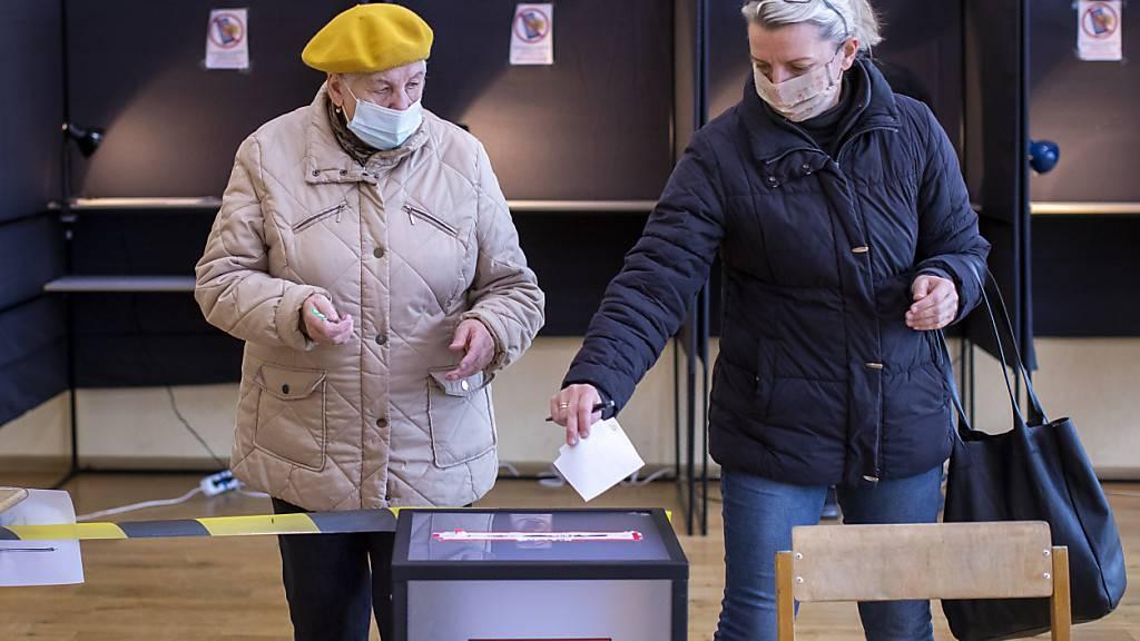 Zwei Frauen bei ihrer Stimmabgabe in einem Wahllokal in der litauischen Hauptstadt Vilnius. Foto: Mindaugas Kulbis/AP/dpa
