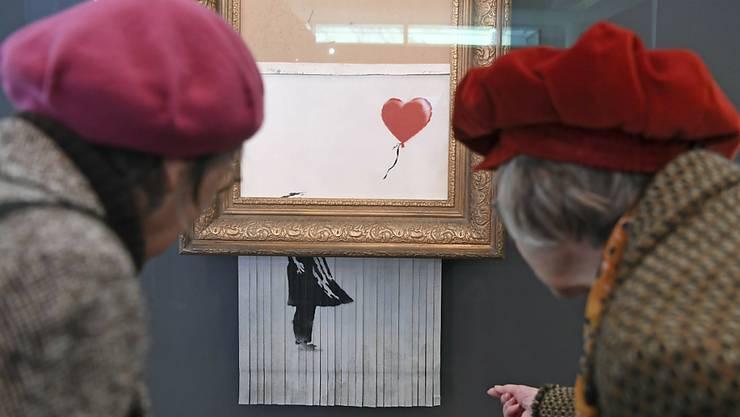 """Hiess mal """"Girl with Ballon"""" und trägt neu den Titel """"Love is in the Bin"""": Das geschredderte Banksy-Werk lockt das Publikum in Scharen ins Museum."""