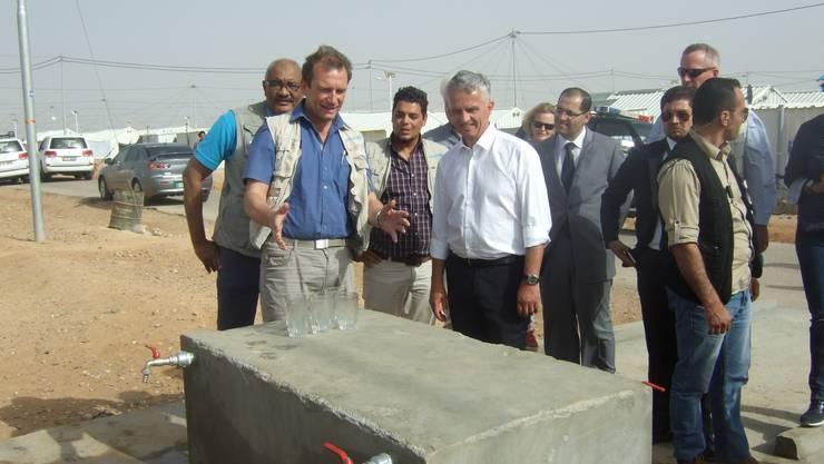 Rainer Prüss stellt Bundesrat Didier Burkhalter die neue Wasserversorgung im Flüchtlingscamp vor, im Bild eine Zapfstelle.