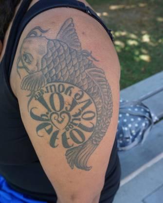 «Der Koi-Karpfen, der den Spruch «Don't forget to love yourself» umkreist, war mein erstes Tattoo. Seit sechs Jahren ziert er meinen Oberarm. Ich schaue durch meine soziale, empathische Art immer zuerst auf die anderen und gehe dabei selbst ein wenig vergessen. Deswegen ist der Spruch zu meinem Lebensmotto geworden. Der Koi steht unter anderem für Glück und Wandelbarkeit. Das Herz im Zentrum symbolisiert meine philippinischen Wurzeln. Das gesamte Tattoo hat eine Kollegin von mir, die Künstlerin ist, designt. Ich steche mir lieber ein Tattoo, als zum Zahnarzt zu gehen.»