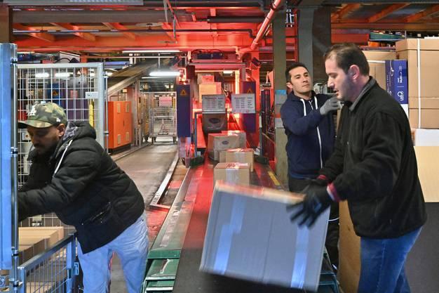 Mitarbeitende hieven die Ware auf ein Förderband.