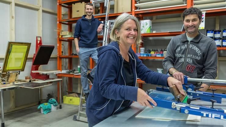 In 65 Ateliers, Werkstätten und Büros wird «im Rüetschi Haus» gearbeitet. Im Siebdruckatelier füllen Caroline Casal, Toni Möri und Ben Fluri (auf der Leiter) die Regale ein.