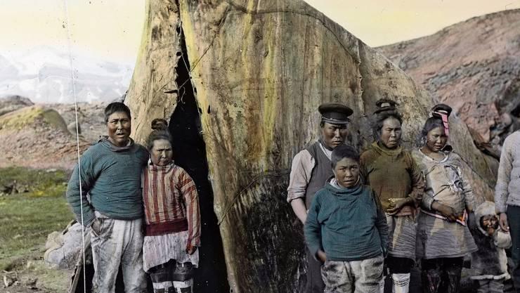 Eine Inuit-Familie an der Ostküste Grönlands vor ihrem Sommerzelt im Jahr 1912. Grönland ist damals sehr dünn besiedelt und gehört zu Dänemark.