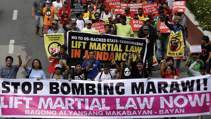 Demonstranten in Manila fordern eine Ende des Kriegsrechts im Süden der Philippinen. Allerdings vergeblich: Das Parlament stimmte der Verlängerung des Kriegsrechts zu.