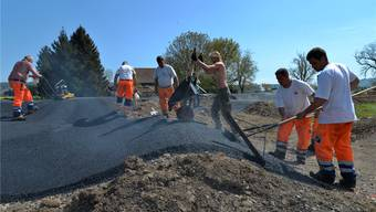 Die Strecke von Hand zu asphaltieren, verlangt den Arbeitern viel Schweiss und Mühe ab.