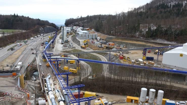 Übersicht auf die 40 000 Quadratmeter grosse Baustelle am Südportal des Sanierungstunnels Belchen. Links flitzen Autos auf der A2 vorbei. 150 Arbeiter werden am Sanierungstunnel arbeiten. Hinter der Baustelle steht das Containerdorf.