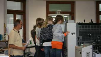 Paul Hurschler weiht die Schülerinnen in die Geheimnisse der Drucktechnologie ein. (Bild rz.)