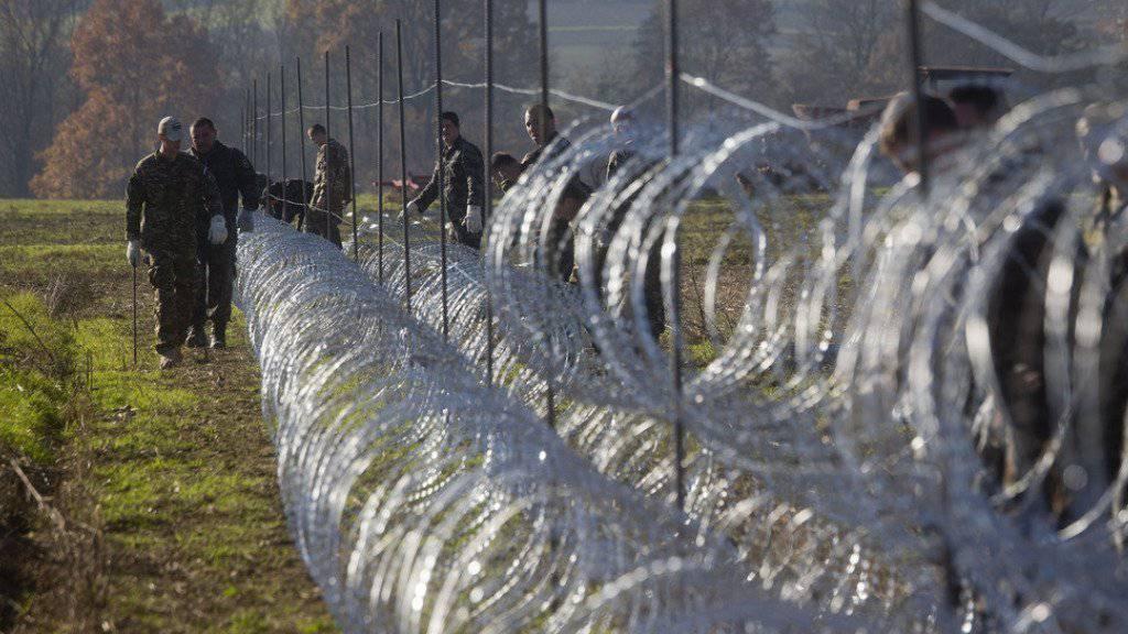 Slowenische Soldaten errichten am Mittwoch einen Stacheldrahtzaun in Gibina an der Grenze zu Kroatien.