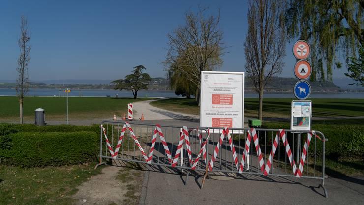 Absperrungen mit Hinweisplakaten mit den Empfehlungen des Bundes zu Social Distancing – ein Park beim Murtensee in Murten.