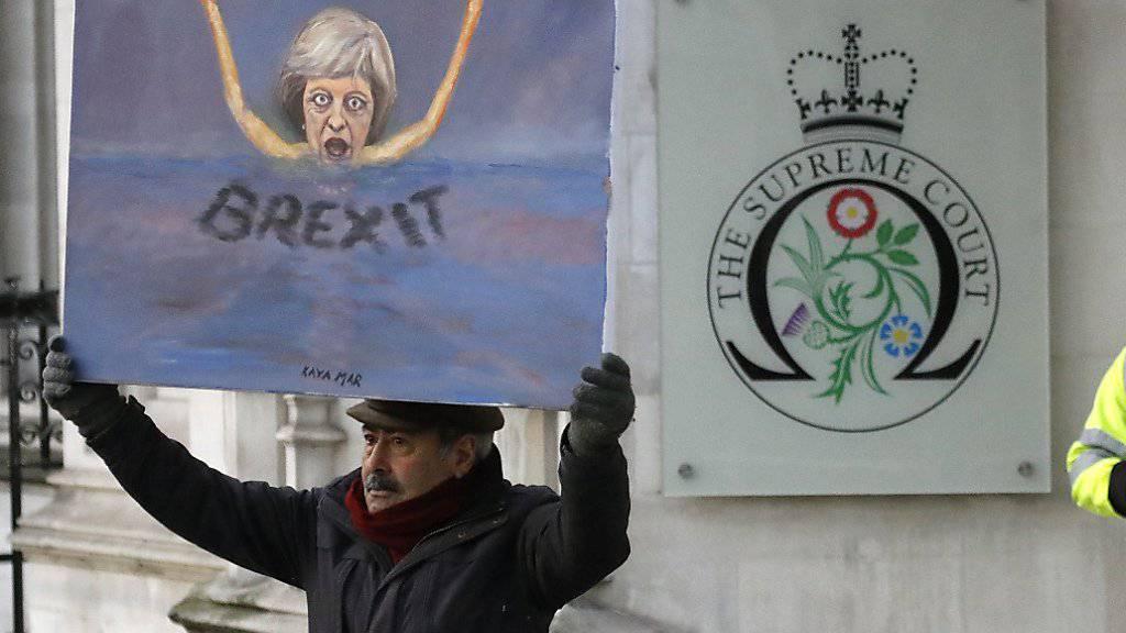 Ein Maler mit einem Bild von Premierministerin Theresa May vor dem Londoner Supreme Court: Dieser hat entschieden, dass das britische Parlament beim EU-Ausstieg mitreden muss.