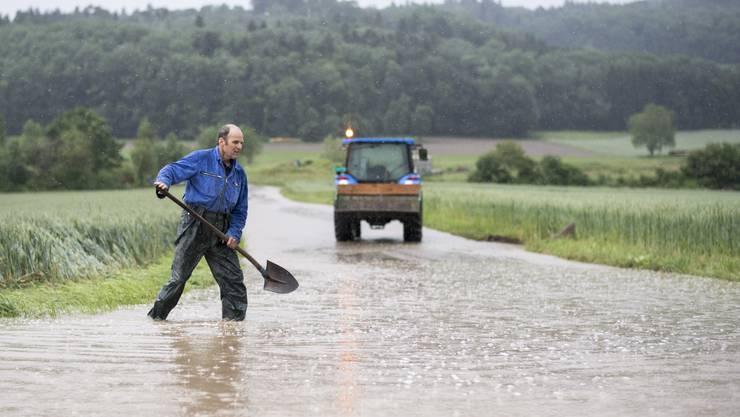 Ein Mann läuft mit einer Schaufel auf einer überfluteten Strasse in Dottikon.