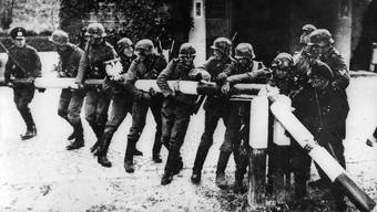 Wehrmachtssoldaten reissen den Schlagbaum an der polnischen Grenze ein: Am 1. September 1939 überfiel Deutschland Polen.