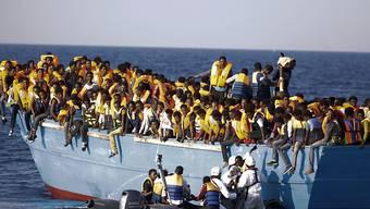 Italienische Helfer retten Bootsflüchtlinge vor der libyschen Küste. Oft werden die Menschen von Schleppern in seeuntüchtige und völlig überladene Boote getrieben. (Bild vom August)