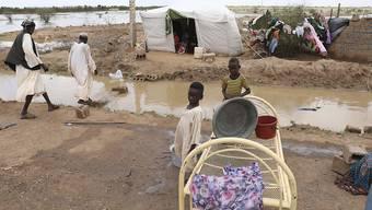 Zwei kleine sudanesische Jungen stehen vor ihrer provisorischen Unterkunft am Straßenrand, etwa 60km von der Hauptstadt entfernt. Sintflutartige Regenfälle haben Häuser und die Infrastruktur im ganzen Land verwüstet. Mehr als 50 000 Menschen sind nach Angaben der Vereinten Nationen betroffen. Foto: Marwan Ali/AP/dpa