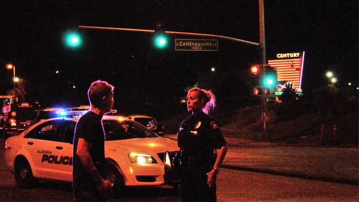 Ein Passant unterhält sich mit einer Polizistin in der Nähe des Kinos, wo der Amoklauf stattfand.