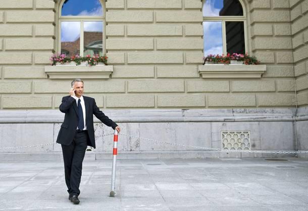 Didier Burkhalter vor dem Bundeshaus am Telefon.