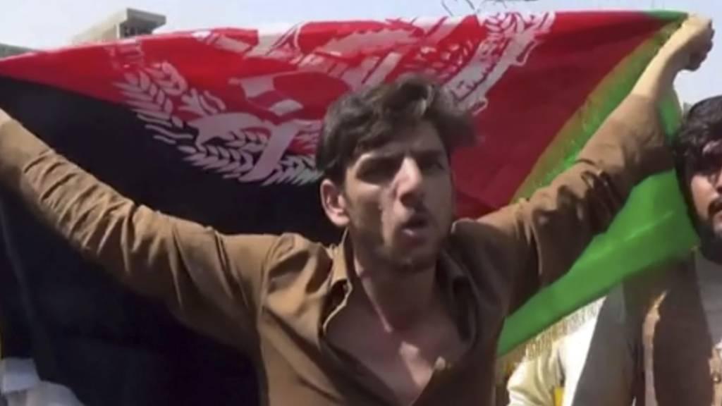 Ein Mann hält die Flagge Afghanistans während einer Demonstration in Jalalabad. Laut Videos in sozialen Medien finden in Afghanistan offenbar trotz des Siegeszugs der militant-islamischen Taliban weiter Demonstrationen mit der Nationalflagge statt. Foto: Uncredited/AP/dpa
