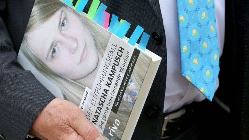 Peter Reichard hält sein Buch vor dem Gericht in Köln.