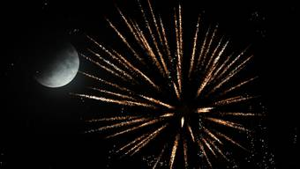 epaselect epa07721193 A partial lunar eclipse rise during a firework at the Brezel festival in Speyer, Germany, 16 July 2019. The partial lunar eclipse on the night of 16 July 2019 will take place 50 years after the astronauts Neil Armstrong, Buzz Aldrin and Michael Collins launched aboard a Saturn V rocket toward the Moon on 16 July 1969. The year 2019 marks the 50th anniversary of the first moon landing on 20 July 1969. EPA/RONALD WITTEK