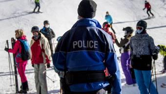 Ansteckungsgefahr beim Anstehen vor dem Sessellift: Ein Polizist kontrolliert in Verbier VS, ob die Schutzkonzepte eingehalten werden.