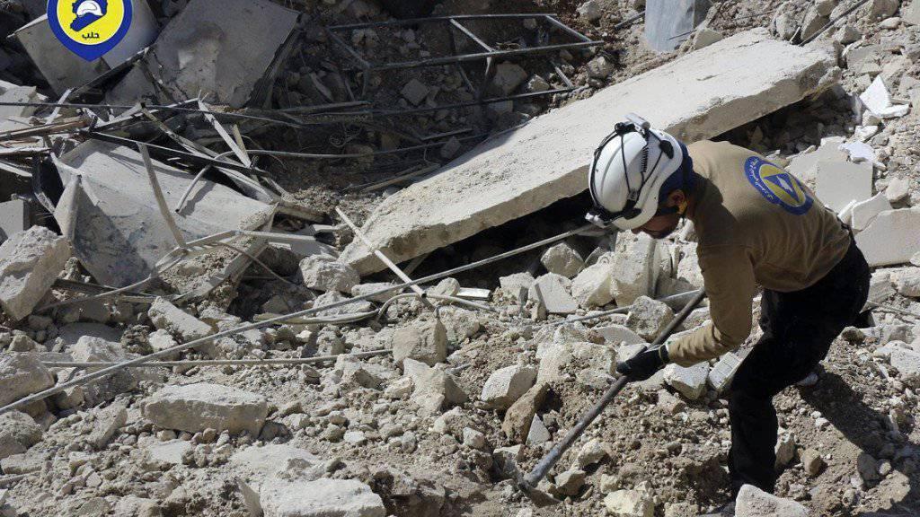 Nach Bombardierungen sucht ein Helfer im Schutt nach Überlebenden. (Archiv)