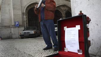 Ein Arbeitsloser spielt für Almosen auf einer Strasse in Lissabon (Archiv)