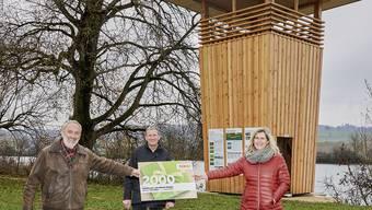 Coop Regionalrätin Sibylle Miescher-Jost übergibt den Check zu Gunsten des Projektes Holzturm Kraftort Wald an Geri Kaufmann (M.) und Thomas Leimer (l.)