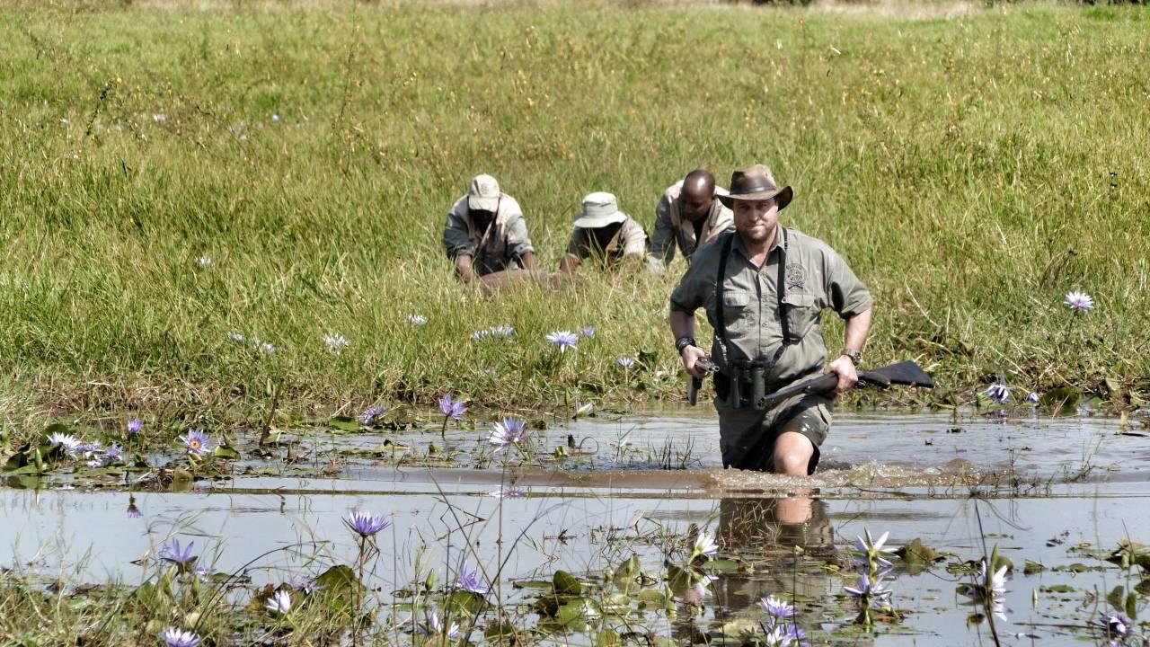 Die Jäger auf der Pirsch. Stephan Stamm watet im Wasser.
