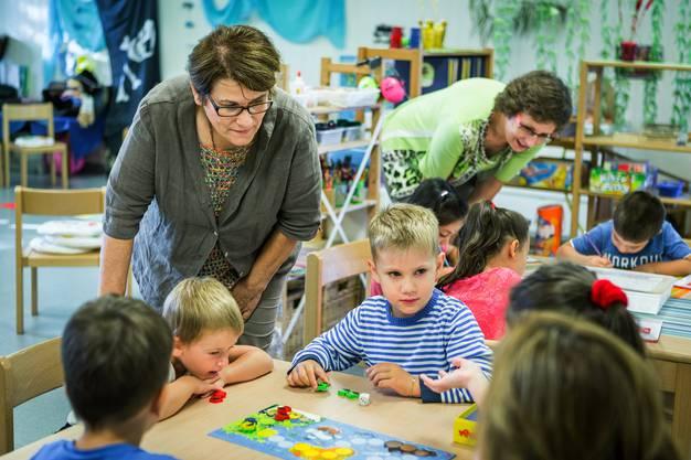 Politiker, hier Grossrätin Trudi Huonder und Sabine Sutter, beide von der CVP, schauten im Kindergarten Fünflinden den Kindern über die Schultern.