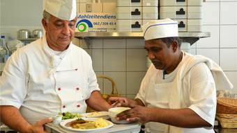 Küchenchef Willi Hürlimann bereitet mit Küchenhilfe Ranga ein Menü für die Auslieferung vor.