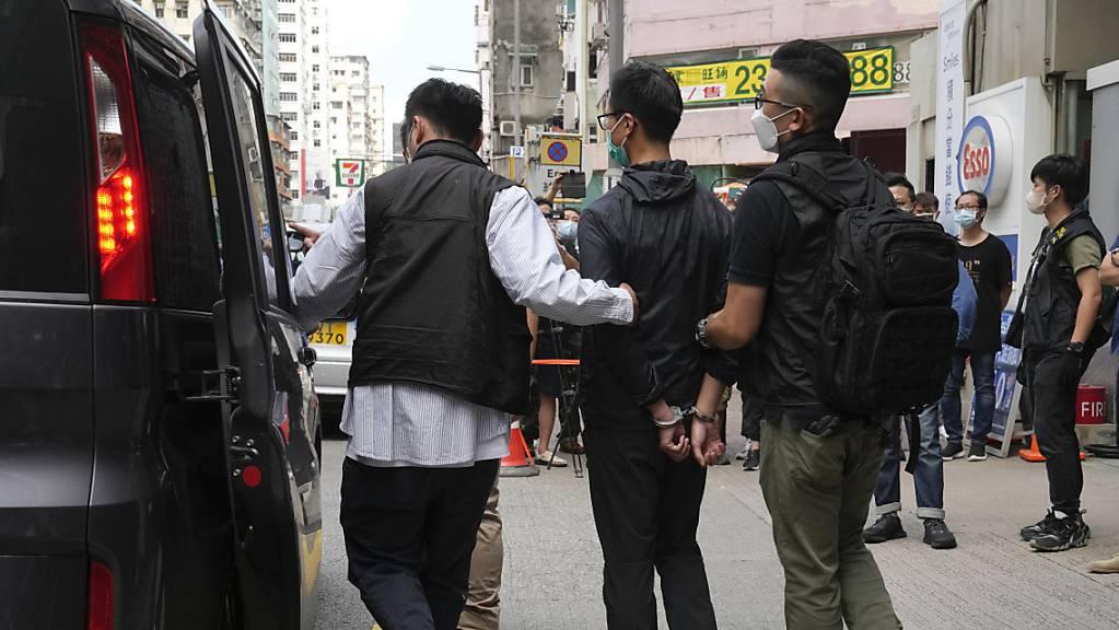 Ein Mitglied des Komitees der Hongkonger Allianz zur Unterstützung der patriotischen demokratischen Bewegungen Chinas, wird eskortiert. Nach der Festnahme von vier führenden Mitgliedern der Demokratiebewegung in Hongkong ist nach Medienberichten ein weiterer Mitstreiter inhaftiert worden. Foto: Kin Cheung/AP/dpa