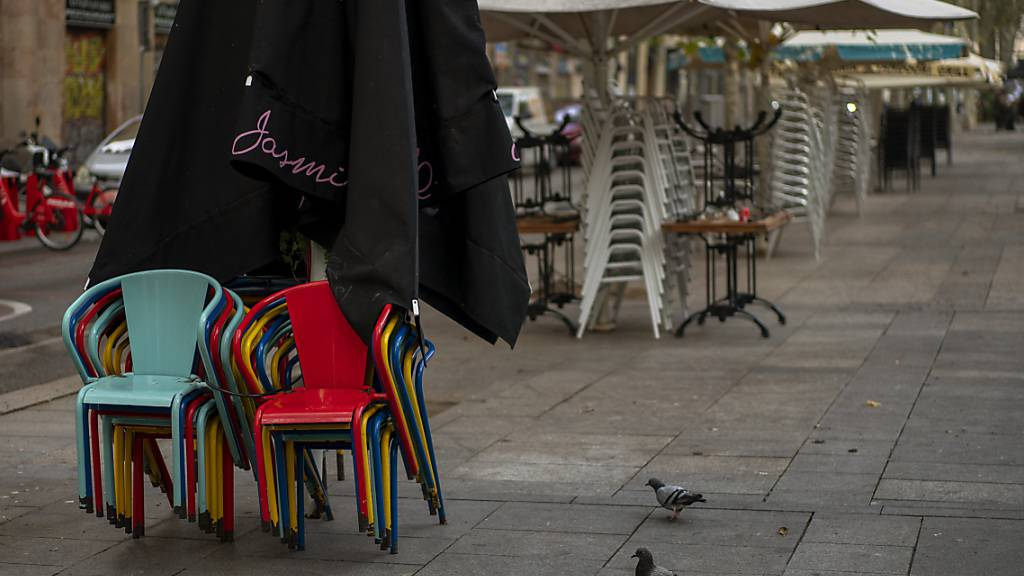 Stühle und Tische stapeln sich auf einer Bar-Terrasse in Barcelona. Foto: Emilio Morenatti/AP/dpa