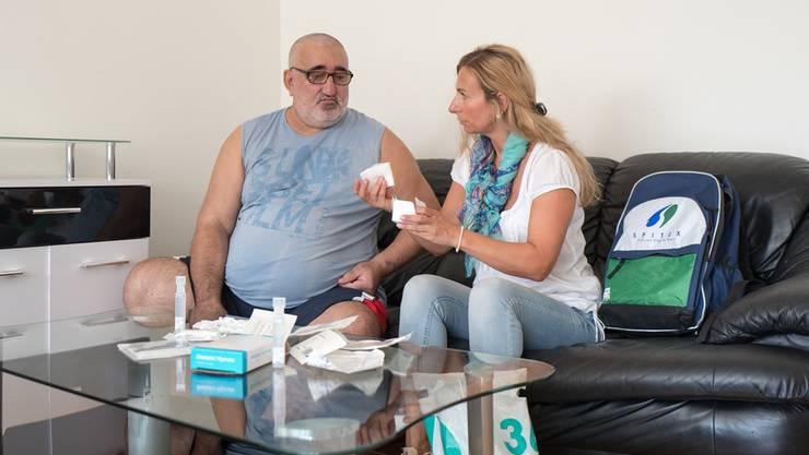 Pflegefachfrau Resmije Jakupi erklärt Radmilo Surdulovic, wie seine Wunde verbunden werden muss.