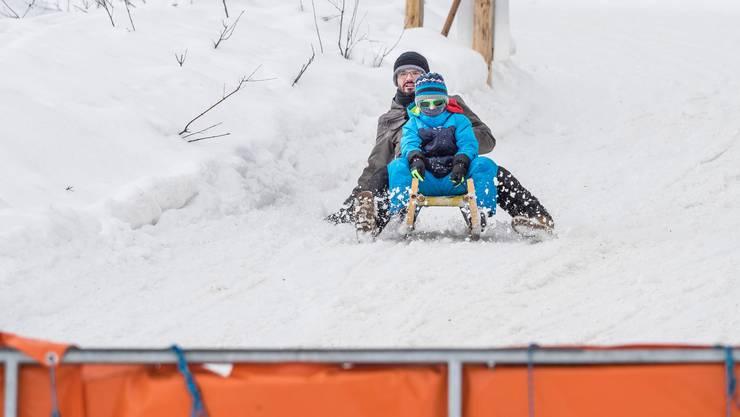 Ein Vater schlittelt mit seinem Kind in Richtung Talstation der Kronbergbahn. Im Vordergrund eine Absperrung, die Schlittler zwingt, abzusteigen.