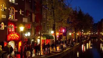 """ARCHIV - Menschen schlendern am Abend an einer Gracht entlang durch den Rotlichtbezirk De Wallen. Nach der Lockerung der Corona-Maßnahmen kommen die ersten Besucher wieder in die Stadt - doch viele Bewohner wollen den Massen-Tourismus nicht mehr. (zu dpa """"Amsterdamer wollen keinen Massen-Tourismus mehr"""") Foto: Koen Van Weel/epa/dpa"""