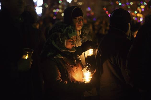 Sie entzündeten Kerzen für die getöteten sechs Männer zwischen 39 und 60 Jahren.