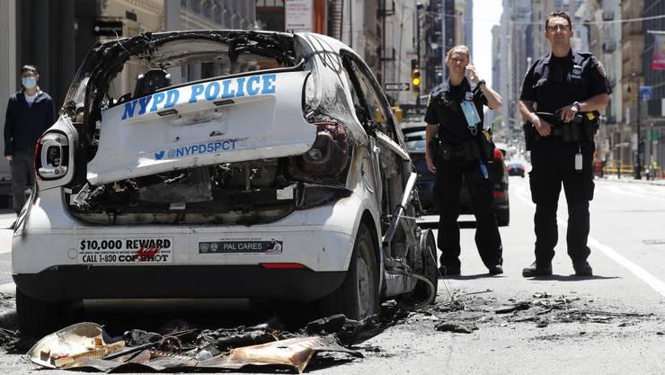 Polizeibeamte in New York City stehen bei einem Streifenwagen, der von wütenden Demonstranten zerstört wurde.