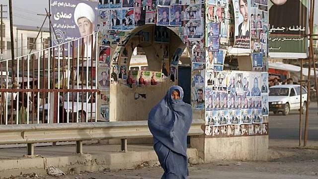 Frau passiert Plakatsäule in Kabul